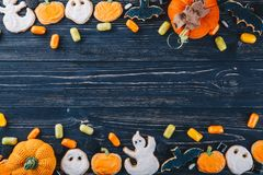 Beautiful gingerbread and sweets for Halloween and pumpkin on the table. Trick or Treat horizontal view from above. Beautiful gingerbread and sweets for stock photography