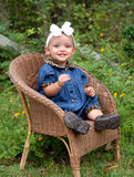 Beautiful Girl. A darling baby girl sitting in a wicker chair wearing denim trimmed in leopard with a big bow in her hair outdoors. She's beautiful Royalty Free Stock Photo