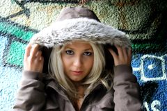 Beautiful girl. Against graffiti wall with hood Royalty Free Stock Image