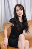 Beautiful girl. A beautiful girl sits sitting on a sofa Stock Photos