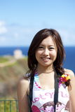 Beautiful girl. A beautiful asian young woman with happy smiling facial expression and flowers in her long hair. She is standing at the lookout at the Kilauea Stock Images