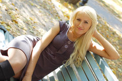 Beautiful girl. Blond girl sits on a bench in autumn park Stock Photos