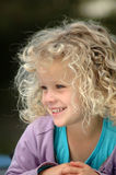 Beautiful girl. A beautiful caucasian white girl head portrait with happy smiling expression in her pretty face and long light blond curly hair watching in the Royalty Free Stock Images