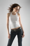 Beautiful girl. Beautiful young model in white t-shirt and jeans on grey background Royalty Free Stock Photography
