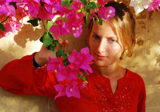 Beautiful girl. A girl stands near a wall with flowers Royalty Free Stock Photography