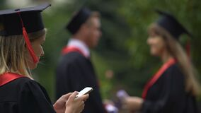 Beautiful girl in academic dress browsing on smartphone, graduation event. Stock footage stock footage