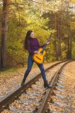 Beautiful girl with acoustic guitar in autumn park stock photography