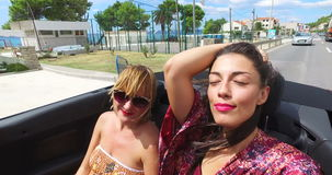 Beautiful girl adjusting hair while riding in windy the back seat of convertible. Beautiful brunette adjusting her hair while riding with her female friend in stock video footage
