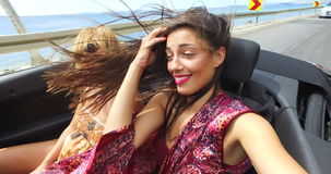 Beautiful girl adjusting hair while riding in windy the back seat of convertible. Beautiful brunette adjusting her hair while riding with her female friend in stock footage