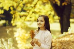 Beautiful girl adolescent. With happy eyes and smiling face holding dry eyellow oak leaf posing in autumn forest on natural background stock photography