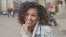 Beautiful girl with afro haircut sitting on bench at city street stock video footage