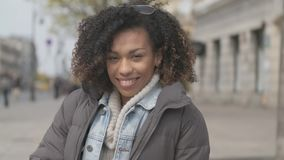 Beautiful girl with afro haircut sitting on bench at city street stock video