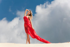 The beautiful girl against clouds. The beautiful girl in red kapron costs against the sky with clouds Stock Photo