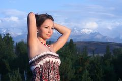 The beautiful girl against mountains. In sunset beams Stock Photo