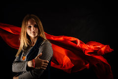 Beautiful girl against red fabric in the dark Stock Photography