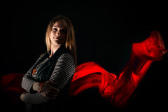 Beautiful girl against red fabric in the dark Royalty Free Stock Image