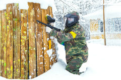 Beautiful girl with air gun playing paintball in winter. Nature Royalty Free Stock Photo