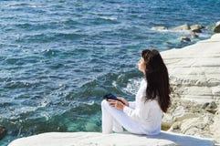 Beautiful girl praying. Beautiful girl sitting alone on the beach and praying to GOD Royalty Free Stock Photography