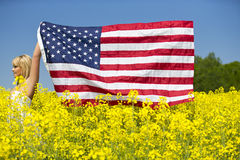 A beautiful girl with american flag in yellow field Stock Photos