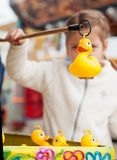 Beautiful girl in the amusement park to catch a toy duckling. Du Royalty Free Stock Image