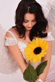 Beautiful girl angel holding a sunflower Stock Photo