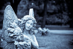 Beautiful girl angel statue. A statue of an angel holding flowers with her wings spread Royalty Free Stock Photos