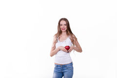 Beautiful girl with an apple on a white background. In a white shirt laughing Royalty Free Stock Image