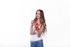 Beautiful girl with an apple on a white background. In a white shirt laughing Stock Photo