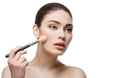 Beautiful girl applying blush with brush royalty free stock photography