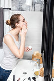 Beautiful girl applying cream in her bathroom with beauty accessories. Healthy beautiful girl with tied hair applying moisturizing face cream for cosmetics stock images