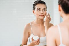 Beautiful girl applying face cream and looking at mirror. In bathroom stock photos