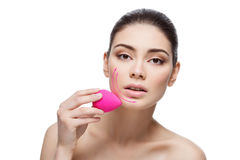 Beautiful girl applying foundation with sponge Royalty Free Stock Photo