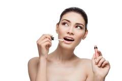 Beautiful girl applying lipgloss Stock Photo