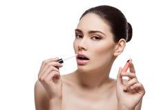 Beautiful girl applying lipgloss Stock Image