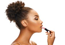 Beautiful girl applying lipstick on her lips. Photo of african american girl in profile on white background. Skin care and beauty royalty free stock images