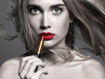 Beautiful girl Applying lipstick. young Woman putting red lipstick Stock Photos