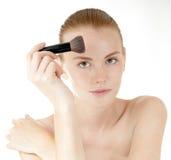 Beautiful girl applying makeup. royalty free stock photography
