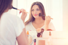 Beautiful girl applying makeup. Beautiful girl looking in the mirror and applying makeup Royalty Free Stock Photos