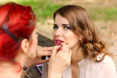 Beautiful girl applying makeup Stock Images