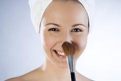 Beautiful girl applying makeup. Beautiful smiling girl applying makeup Royalty Free Stock Photos