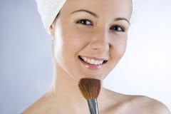 Beautiful girl applying makeup. Beautiful smiling girl applying makeup royalty free stock images