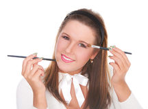Beautiful girl applying makeup with two brushes Royalty Free Stock Photos