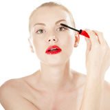 Beautiful girl applying mascara on her eyelashes. Royalty Free Stock Photos
