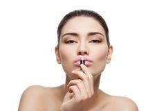 Beautiful girl applying pink lipstick Stock Photo