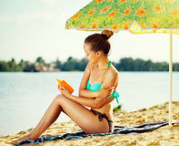 Beautiful girl applying sun tan cream on her skin Royalty Free Stock Photos