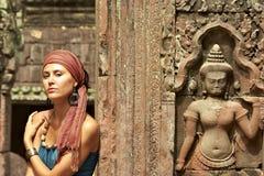 Beautiful girl and Apsara. Beautiful girl near Apsara bas-relief in Angkor temple Royalty Free Stock Image