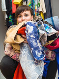 Beautiful girl with an armful of clothes in her hands Royalty Free Stock Images