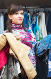 Beautiful girl with an armful of clothes in his hands Royalty Free Stock Image