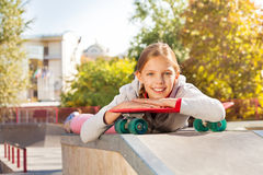 Beautiful girl with arms on red skateboard laying Royalty Free Stock Image