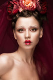Beautiful girl with art creative make-up in image of red bride for Halloween. Beauty face. Beautiful girl with art creative make-up in the image of a red bride Stock Image